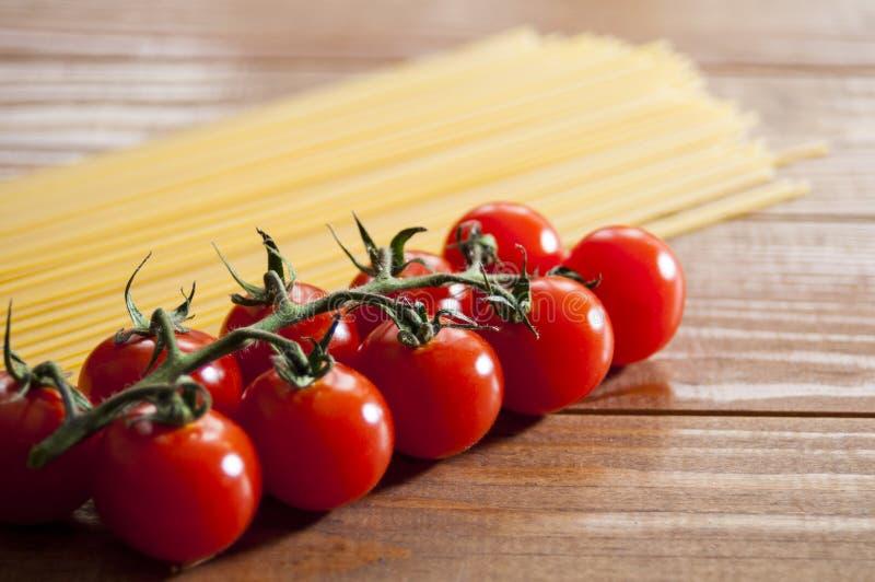 Spaghetti en kersentomaten op een houten lijst Eigengemaakt voedsel of restaurant Ingrediënten voor het koken Nationale Italiaans royalty-vrije stock foto's