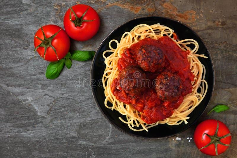 Spaghetti en vleesballetjes met tomatensaus, boven mening over een donkere steenachtergrond stock foto