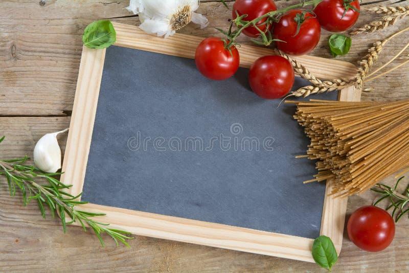 Spaghetti entiers de grain avec des oreilles, des tomates et des herbes de blé sur W image stock