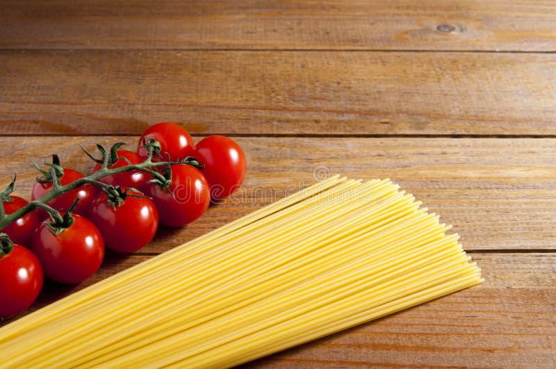 Spaghetti et tomates-cerises sur une table en bois Tomates à la gauche des spaghetti Nourriture ou restaurant faite maison Ingréd images libres de droits