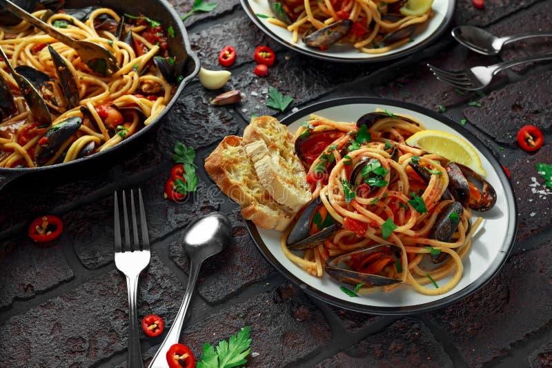 Spaghetti faits maison de pâtes avec la sauce de moule et tomate, les piments et le persil sur le fond rustique Repas de fruits d images stock