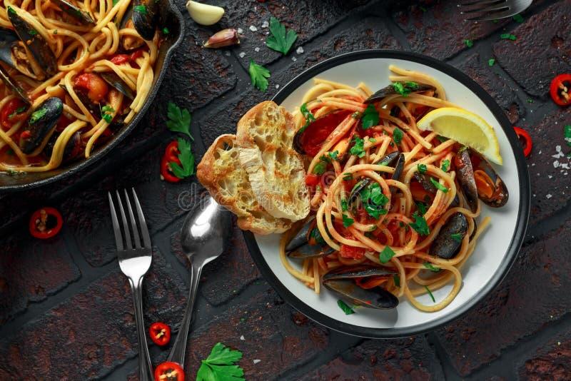 Spaghetti faits maison de pâtes avec la sauce de moule et tomate, les piments et le persil sur le fond rustique Repas de fruits d images libres de droits