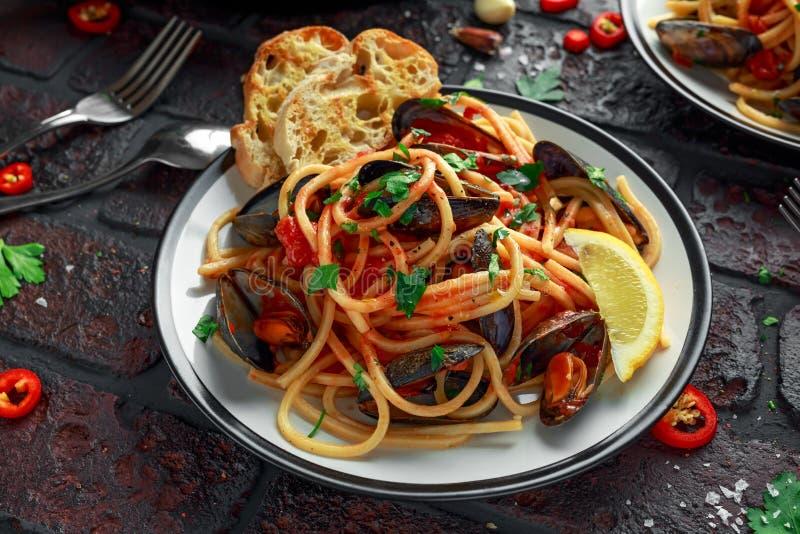 Spaghetti faits maison de pâtes avec la sauce de moule et tomate, les piments et le persil sur le fond rustique Repas de fruits d photo stock
