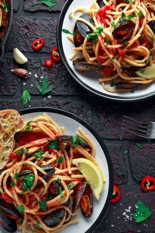 Spaghetti faits maison de pâtes avec la sauce de moule et tomate, les piments et le persil sur le fond rustique Repas de fruits d photos libres de droits