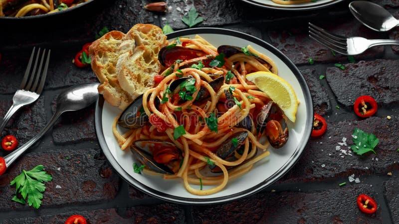Spaghetti faits maison de pâtes avec la sauce de moule et tomate, les piments et le persil sur le fond rustique Repas de fruits d image libre de droits
