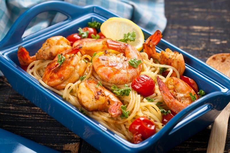 spaghetti faits sauter à feu vif avec les crevettes et les tomates grillées - style italien de nourriture de fusion photos libres de droits