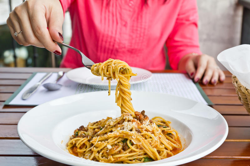 Spaghetti on the fork. Spaghetti noodles with meat sauce on white plate royalty free stock images