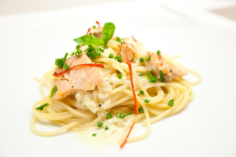 Spaghetti with salmon, cream cheese and spinach close-up on white plate stock photos