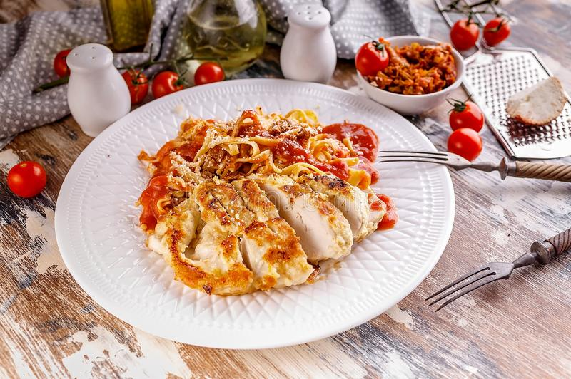 Spaghetti with grilled chicken fillet with tomato sauce on a white plate. Traditional Italian Mediterranean cuisine royalty free stock photo
