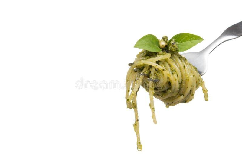 Spaghetti with homemade pesto sauce on fork, isolated on white background. Spaghetti with pesto homemade genovese sauce on fork, isolated on white background stock photo