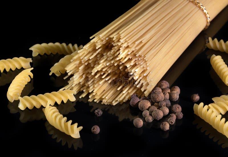 Spaghetti italiani, isolati contro i precedenti neri Pasta italiana gialla, pepe nero immagine stock