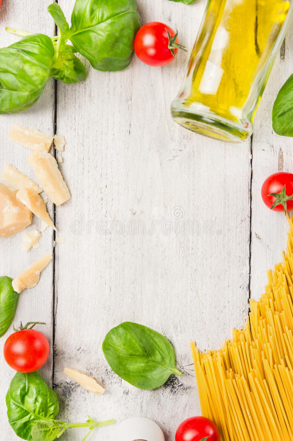 Spaghetti kokende ingrediënten: olie, basilicum, tomaten en parmezaanse kaas op witte houten achtergrond, kader royalty-vrije stock foto's