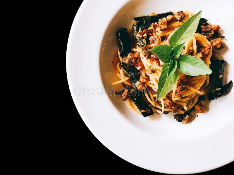 Spaghetti kruidig fijngehakt varkensvlees op geïsoleerde zwarte stock foto