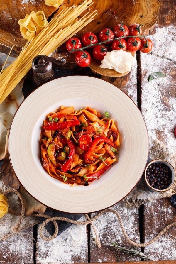 Spaghetti méditerranéens faits maison sains de plat avec la sauce tomate dans la cuvette blanche, ingrédients pour la cuisson images libres de droits