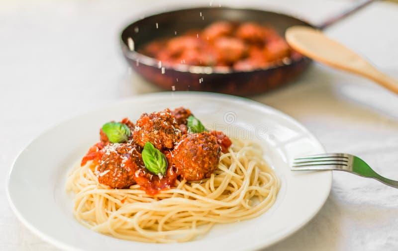 Spaghetti makaron z klopsikami w pomidorowym kumberlandzie, ser spada nad nim obrazy stock