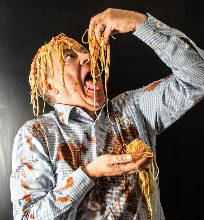 Spaghetti mangeurs d'hommes avec la sauce tomate dans la tête photographie stock libre de droits