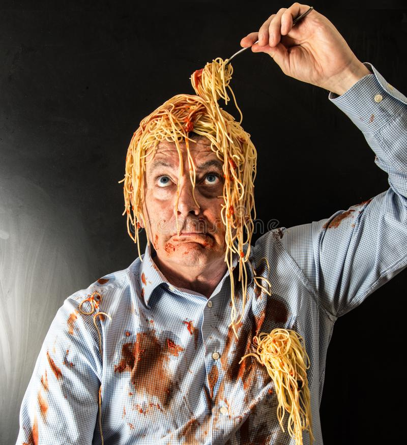 Spaghetti mangeurs d'hommes avec la sauce tomate dans la tête photographie stock
