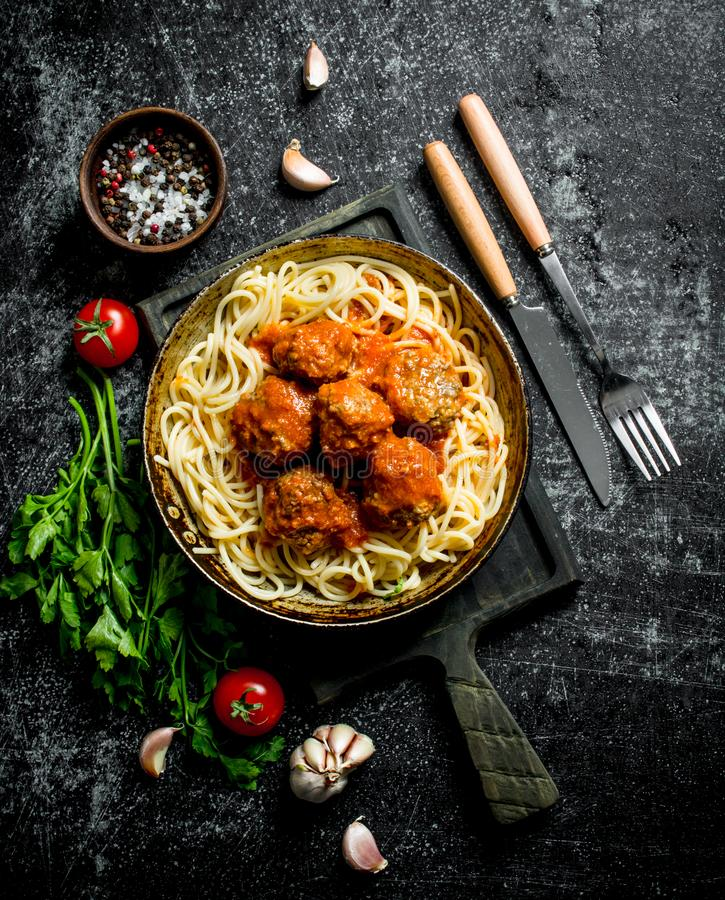 Spaghetti and meat balls in pan with spices, herbs and tomatoes stock photography