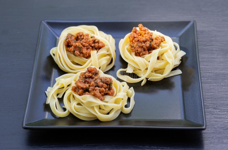 Spaghetti with meat laid out on black square plate royalty free stock photo