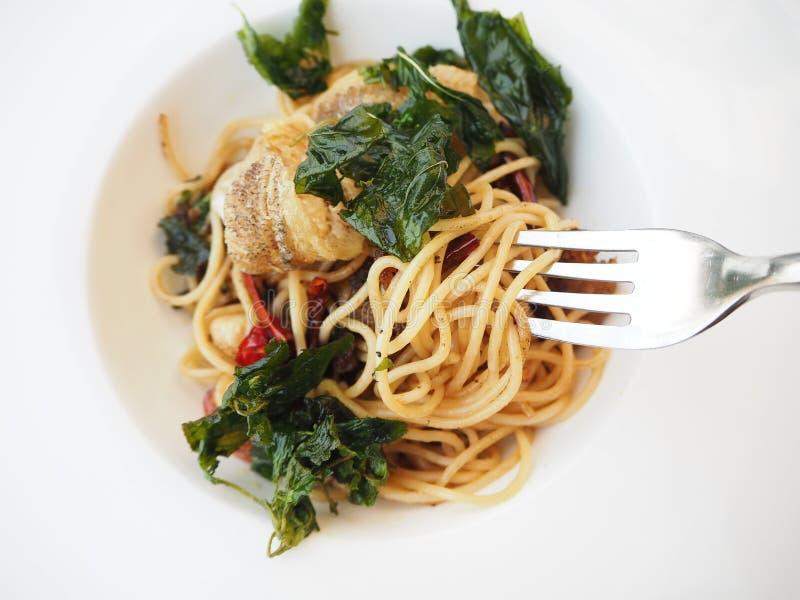 Spaghetti met knoflook, olijfolie, Spaanse peper, en knapperige vissen stock foto's