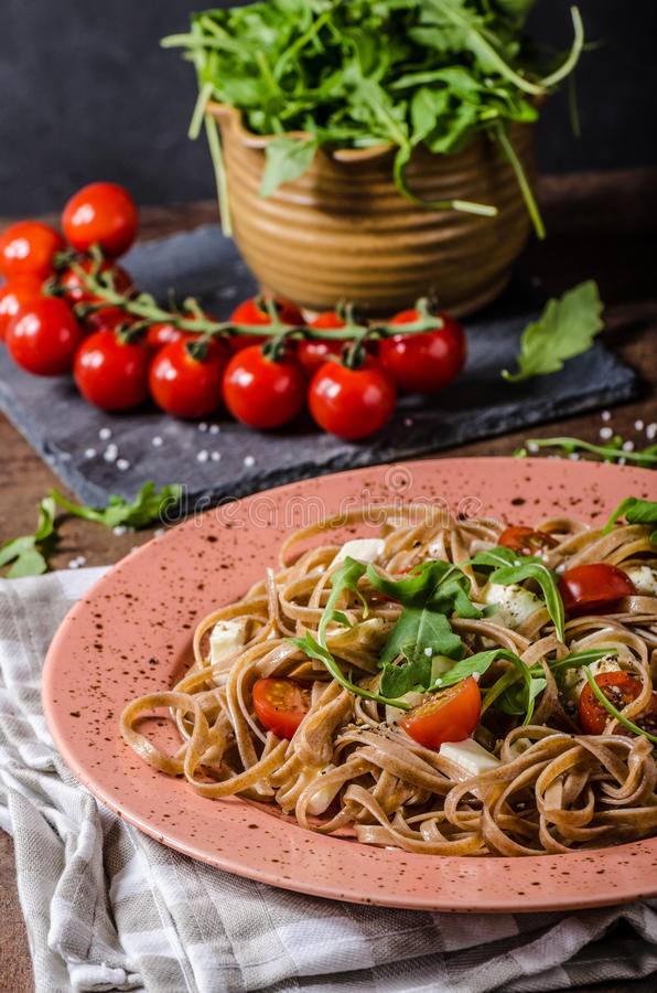 Spaghetti with mozzarella, cherry tomatoes and arugula stock photo