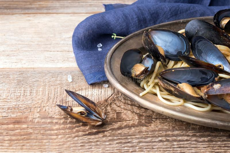 Spaghetti with mussels, tomatoes in spicy sauce in the original plate on the old wooden table. Clams Mytilus closeup. stock photo