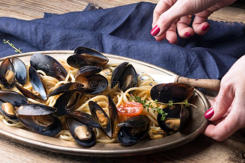 Spaghetti with mussels, tomatoes in spicy sauce in an original plate on an old wooden table. Mollusks Mytilus close up. Italian pasta. A dish for a romantic royalty free stock photography