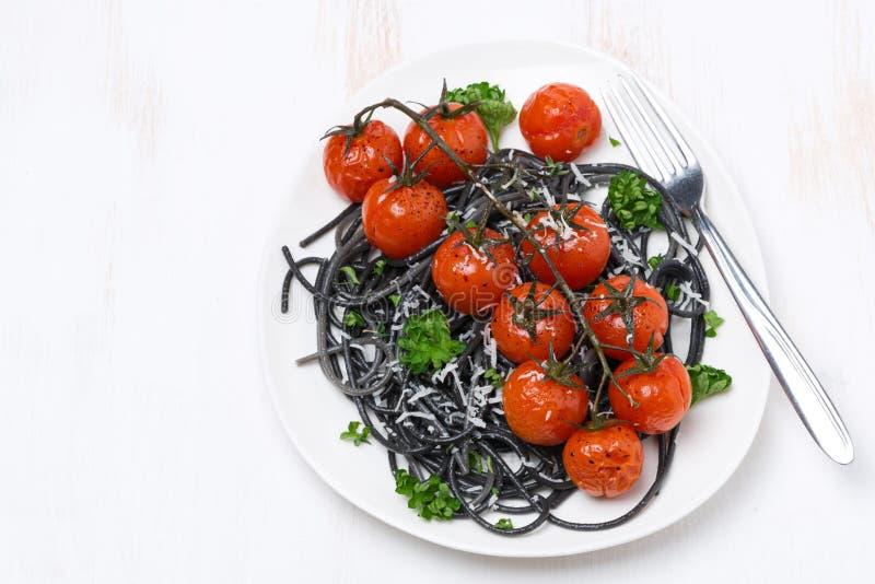 Spaghetti neri con i pomodori arrostiti, vista superiore immagine stock