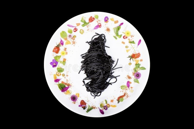 Spaghetti neri del calamaro in piatto con la decorazione del fiore su fondo nero fotografia stock