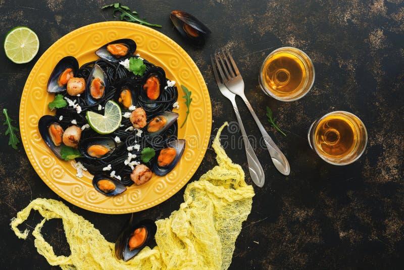 Spaghetti neri della pasta con frutti di mare e vino bianco su un fondo rustico scuro Spaghetti neri con le cozze, pettini, verdi fotografia stock libera da diritti