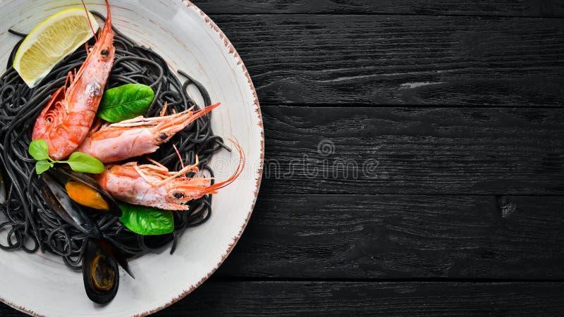 Spaghetti neri Paste nere con frutti di mare ed il limone Gamberetto e cozze Sui vecchi precedenti fotografie stock libere da diritti