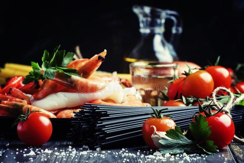 Spaghetti neri, pomodori ciliegia, vino bianco, gamberetto, calamaro, sti immagini stock
