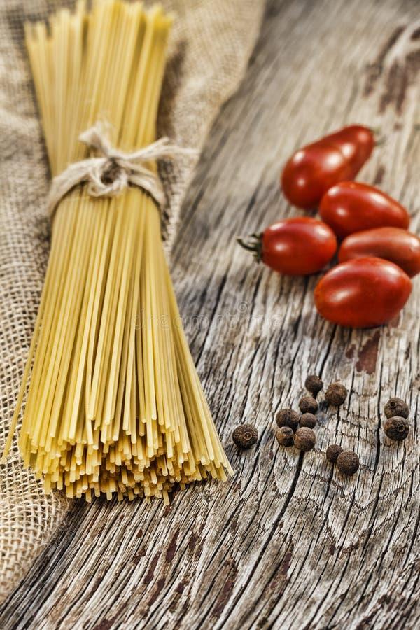Spaghetti o fettuccine e pomodori ciliegia crudi su una tavola di legno Stile rustico immagini stock libere da diritti