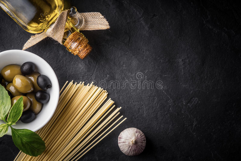Spaghetti, olives and olive oil on the black stone table royalty free stock photo