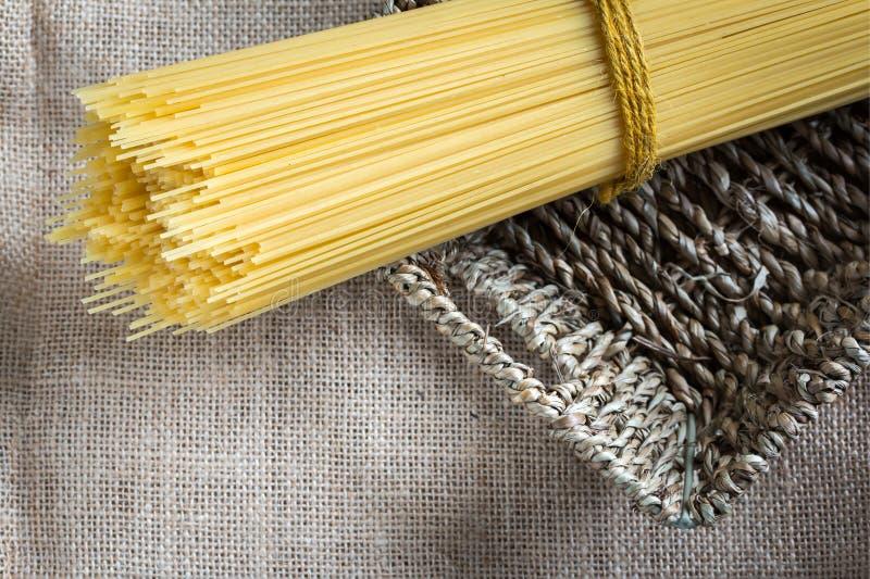 Spaghetti ongekookt in mand stock afbeelding