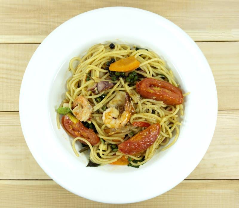 Spaghetti owoce morza w naczyniu na bia?ym drewnianym pod?oga stole zdjęcie royalty free