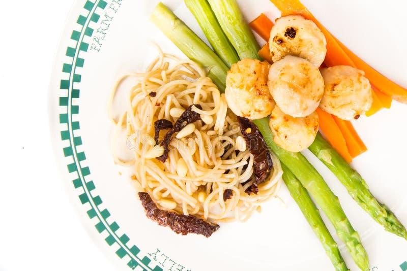 Spaghetti pasta aglio e olio with scallops. Isolated in white stock photo