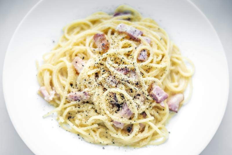 Spaghetti pasta carbonara with bacon ham cream and kampot pepper royalty free stock images