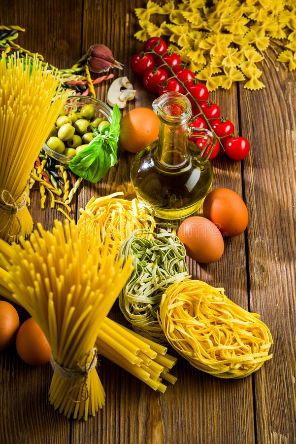 Spaghetti on and pasta on the kitchen table with chicken eggs and olives and tomatoes and basil and spices stock image