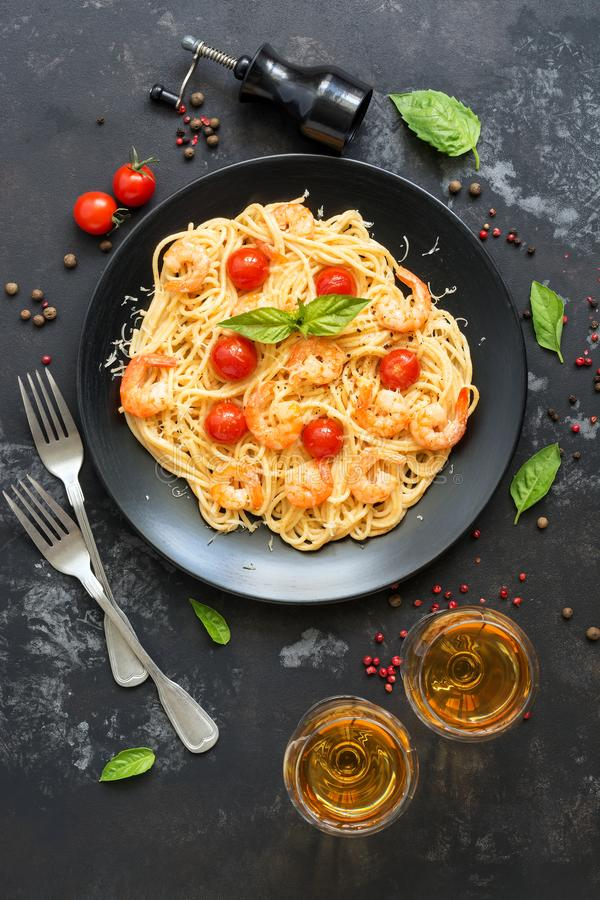 Spaghetti pasta with shrimps and white wine on a dark stone background. Top view royalty free stock photos