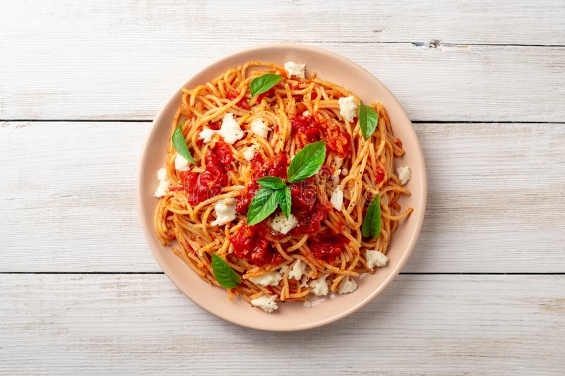 Spaghetti pasta with tomato sauce, mozzarella cheese and fresh basil in plate on white wooden background royalty free stock image