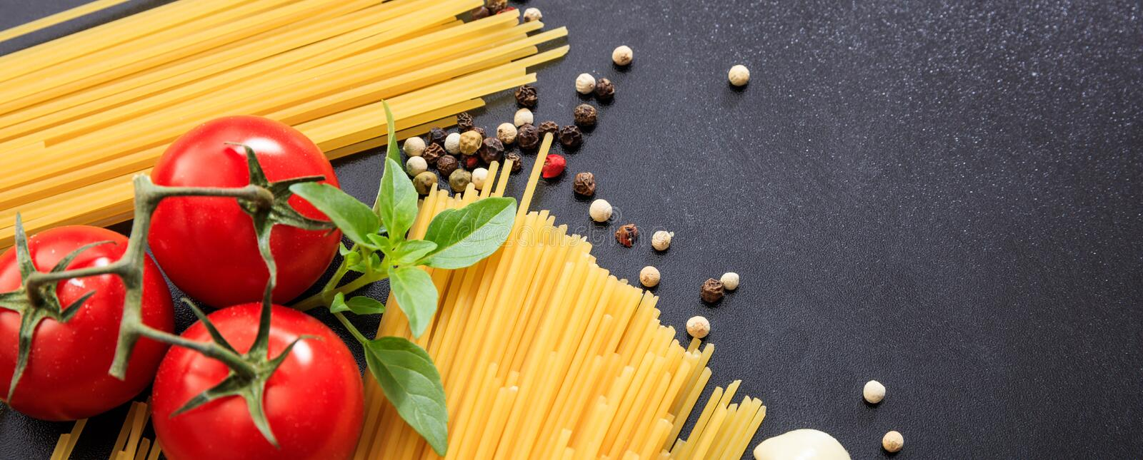 Spaghetti pasta, tomatoes, garlic and basil on black background, banner stock images