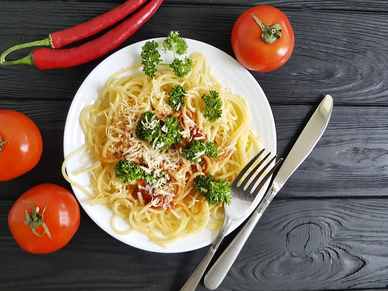 Spaghetti on a plate, fork tomato parsley on a black wooden background. Spaghetti on a plate, tomato parsley a black wooden background fork stock image