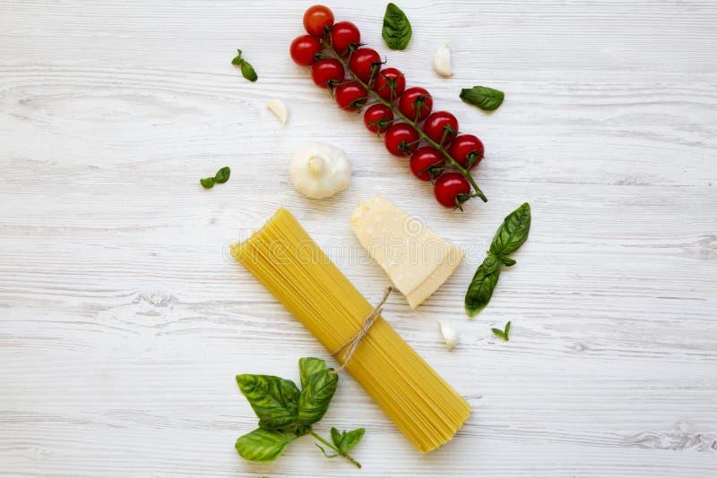 Spaghetti, pomidory, basil, parmesan, czosnek Składniki dla kulinarnego włoskiego makaronu na białym drewnianym stole, mieszkanie zdjęcie royalty free