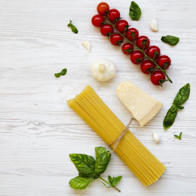 Spaghetti, pomodori, basilico, parmigiano, aglio Ingredienti per la cottura della pasta italiana su un fondo di legno bianco, dis immagini stock