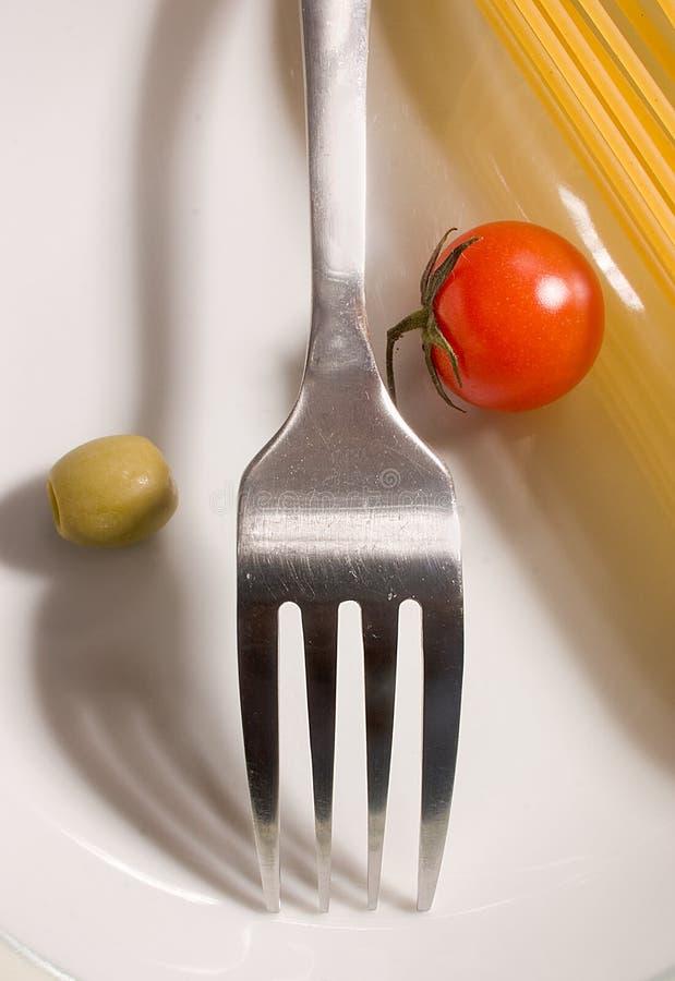 Spaghetti, pomodoro ed oliva grezzi con la forcella fotografia stock