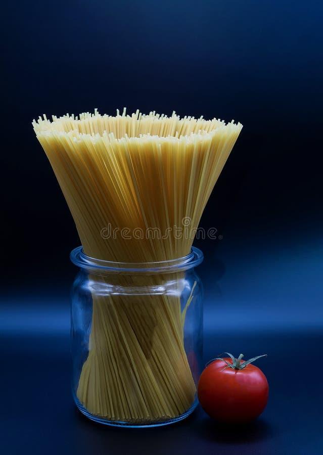 Spaghetti pozycja w trasparent szklanym słoju na błękitnym tle fotografia stock
