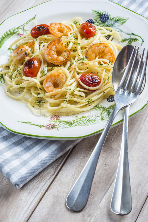 Spaghetti with prawns and grape tomatoes. Garnished with oregano and parsley royalty free stock image