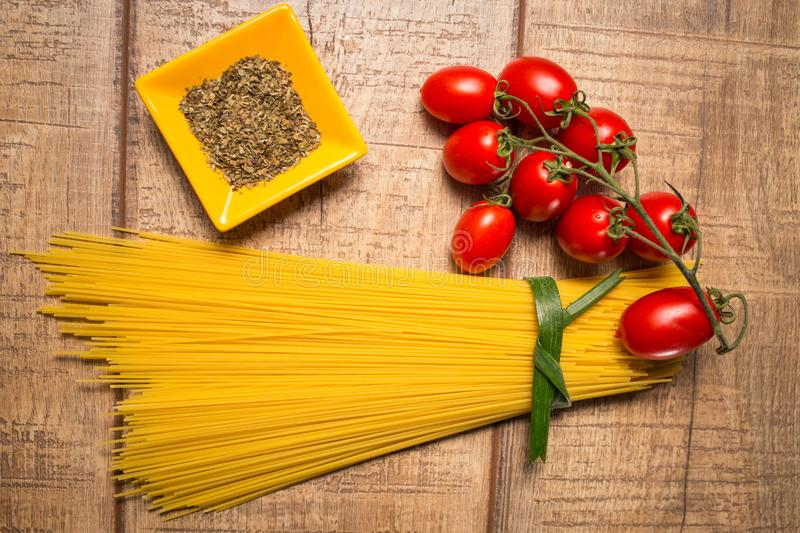 Spaghetti and Roma tomatoes isolated on wood table background. Uncooked Italian dried spaghetti. Top view. stock photo