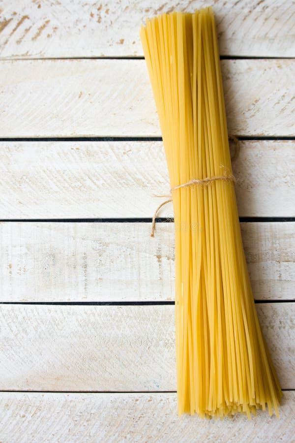 Spaghetti s'étendant sur le contexte léger en bois photographie stock